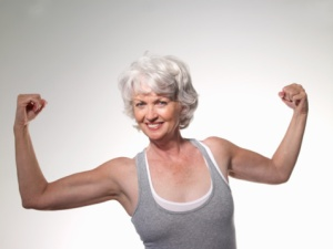 Senior woman flexing muscles, smiling, portra